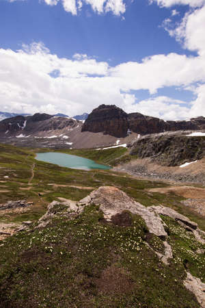 rockies: Portrait view of a glacial lake surrounded by alpine meadows and snow-capped peaks, in the Canadian rockies.