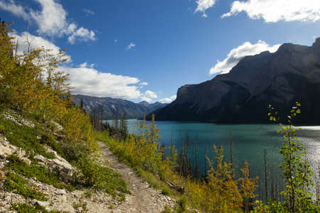 canadian rockies: Fall in the Canadian rockies, the turquoise waters of Lake Minnewanka surrounded by mountains and falling leaves.