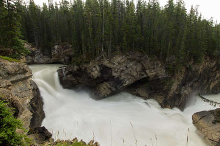 rushing: A rushing waterfall fills a circular pool with foamy water before it leaves via another waterfall. Stock Photo