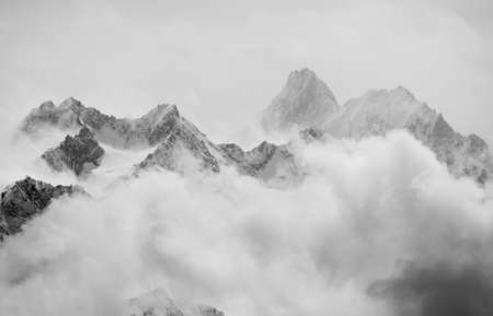 fog white: Atmospheric clouds linger around the peaks of the Swiss alps after a spring snow storm. Stock Photo
