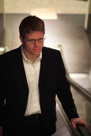 businessman going up escalator