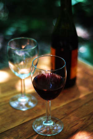sip: wine glasses and bottle on outdoor table