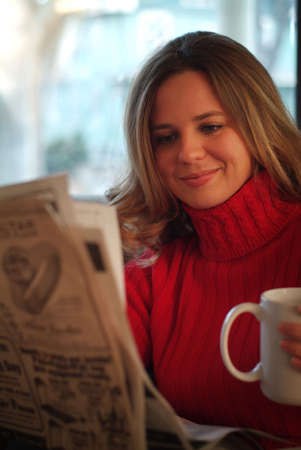 sip: Woman reading newspaper with beverage at home.