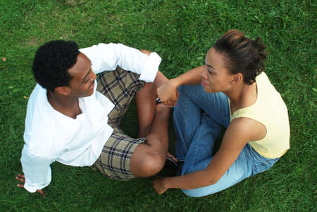 young couple holding hands on grass in park