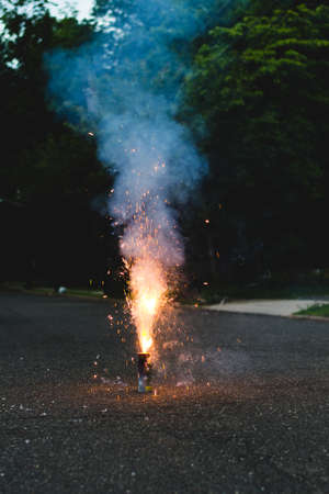 Small firework cake exploding on a the street