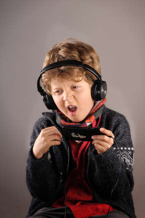 cel: Boy enjoying music with headphones and singing Stock Photo