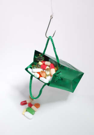 full suspended: Fishing hook holding a bag with medicines
