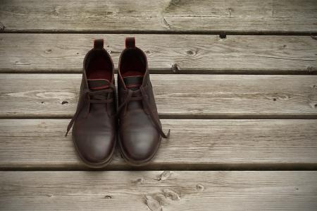 Dark brown boots on wooden floor photo