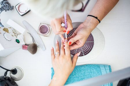 Closeup of Manicurist Applies Nail Gel Polish on Finger. Girl client holds hand on the client on Towel. Beautician gently manicured service