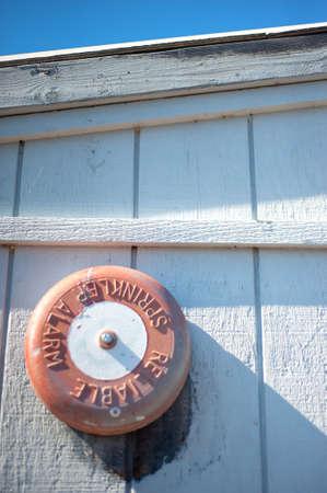sprinkler alarm: Orange Fire Sprinkler Alarm on Side of White Shed With Some Blue Sky