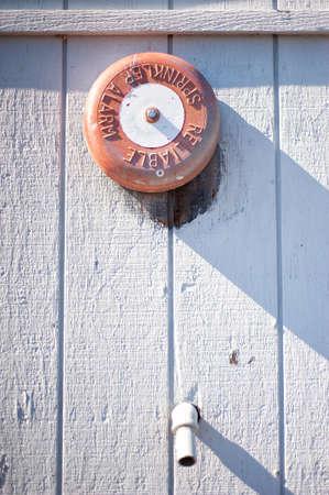 sprinkler alarm: Orange Fire Sprinkler Alarm on Side of White Shed With Water Valve Below Stock Photo