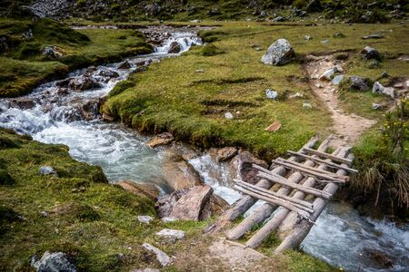 salkantay: A wooden bridge on lush green landscape of Peru.