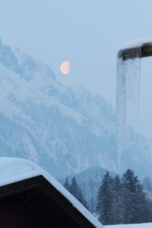 the moon over the austrian mountains in winter photo