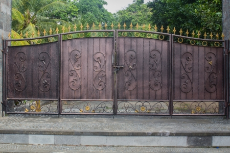 iron gate: an old iron gate in front of a house in Bali Stock Photo