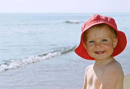 海によって赤い帽子との幸せな笑顔の女の子 写真素材