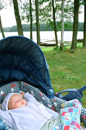 湖、新鮮な空気と自然環境によってキャリッジで眠っている赤ちゃん