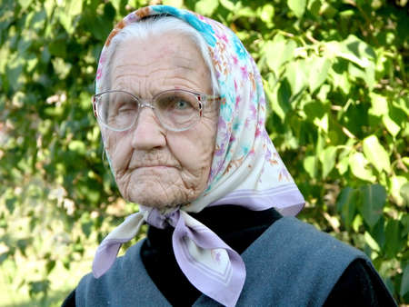 Old grey woman with headscarf against green leaves background