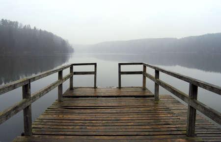 霧の湖の秋の風景の静かな上のレールと孤独な桟橋