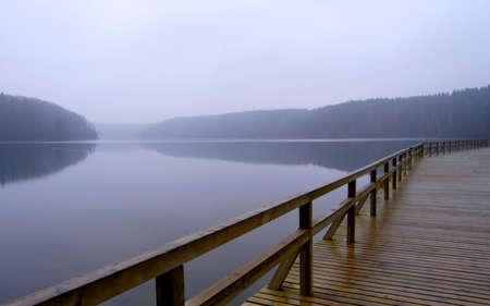 霧の湖、遅い秋の風景の静かなレールと孤独な桟橋 写真素材