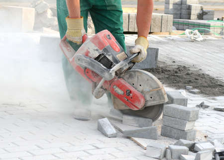 Close look at the worker with concrete saw in his hands and working, dusty workplace Stock Photo