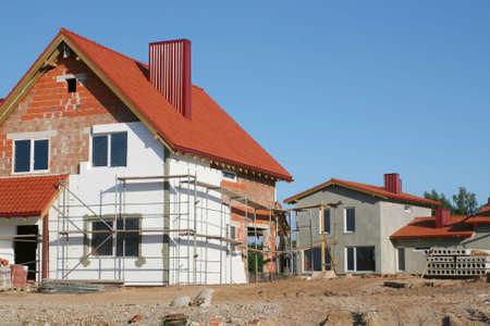 青い空と明確な夏の日の空の新しい家の建設サイト