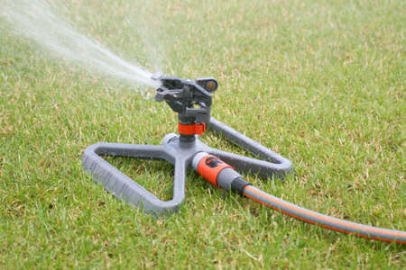Lawn sprinkler spraying water over green grass at summer Stock Photo - 1157067
