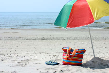 ビーチバッグ、フリップフ、青い海と砂に対して傘
