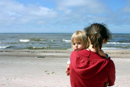 海のそばに立っている彼女の手には小さな娘を持つ母
