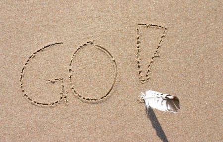 感嘆符と本物の羽が付いている砂に書かれて行くのスローガン