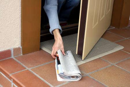 オープンドアを通って朝刊を拾う女性 写真素材
