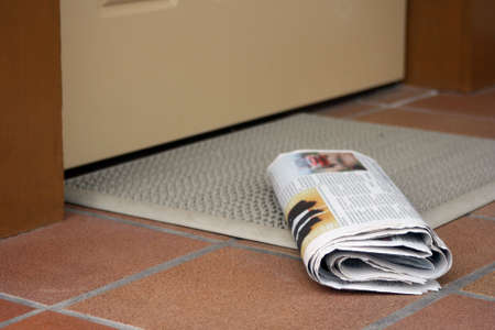 Daily newspaper waiting to be picked up outside home entrance door