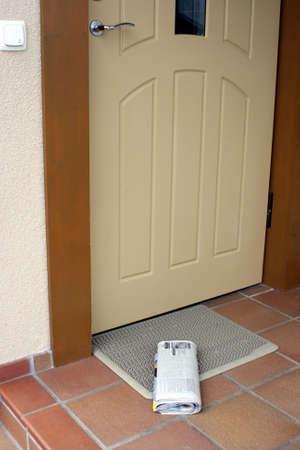 入り口のドアを外にある日刊紙