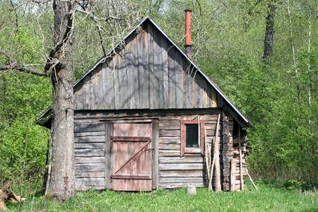 日当たりの良い夏の日に森林でぼろぼろと abbandoned 木造の小屋 写真素材