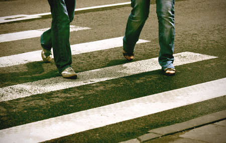 Deliberate high contrast picture of two pedestrians crossing crosswalk
