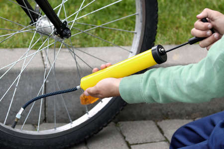 Boy pumping bicycle tyre, close-up on hands