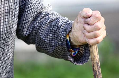 古い木製の棒を持っている女性の手に疲れて