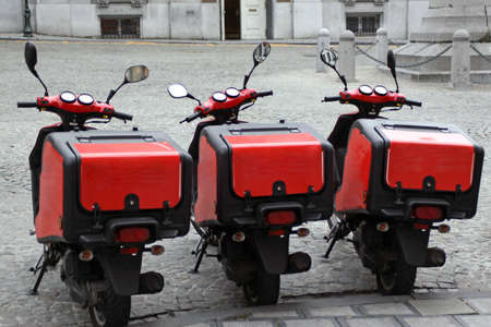 Real street picture of three pizza delivery scooters standing on the street