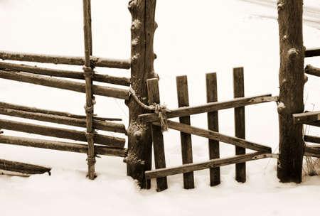 Old wooden rotten fence gate in winter landscape