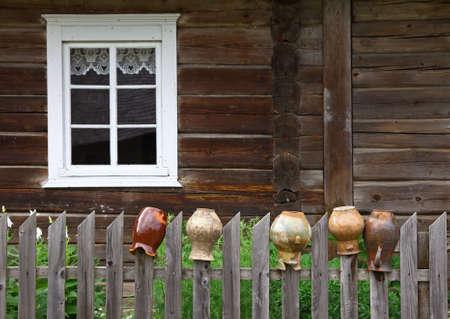 ウィンドウと木製のフェンスに古い水差しのある古い民家の絵