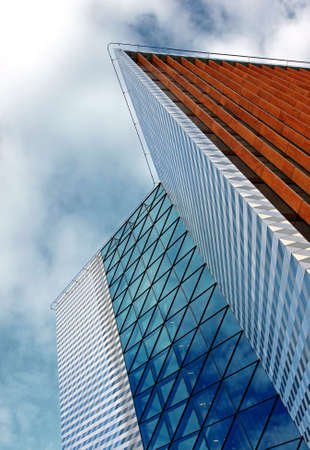 雲と青い空の下で近代的なオフィスビル 写真素材