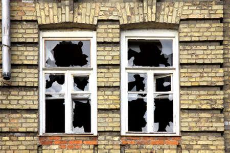 古い放棄されたれんが造りの建物の 2 つの壊れた窓