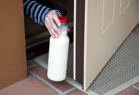Human hand picking a bottle of milk at doorstep