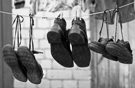 三組の古い靴を洗濯物をぶら下げ
