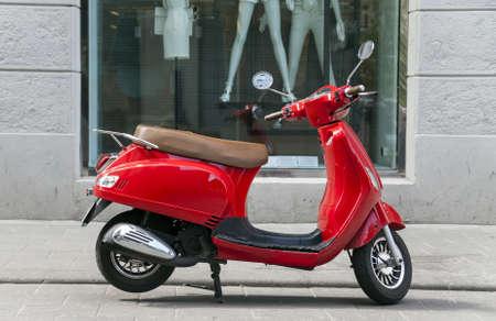 空の通りの上に赤のスタイリッシュなスクーター立って