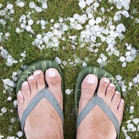 雹を伴う嵐後出身と草の上に立ってフリップフ ロップを持つ男