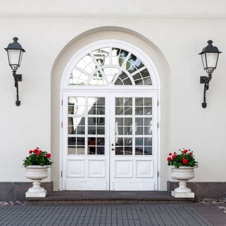 Elegant classic style double glass paned front door with front lanterns and flower pots