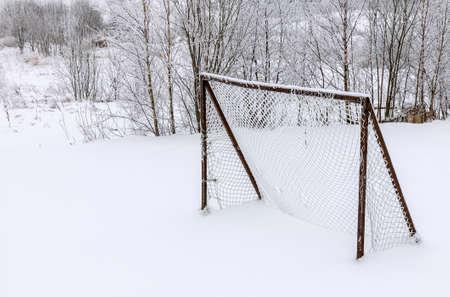 冬のシーズン中に雪で覆われた古い放棄された木製サッカー ゴール 写真素材