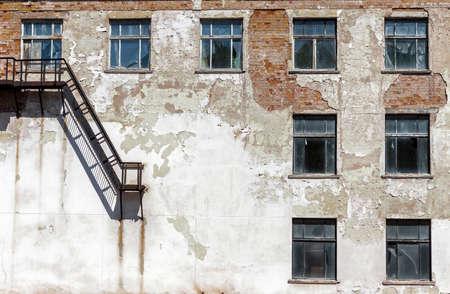 グランジ アーキテクチャの詳細。金属製の階段と壊れた窓の古い廃工場 写真素材