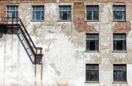 Grunge architecture details. Old abandoned factory with metal staircase and broken windows Stock Photo