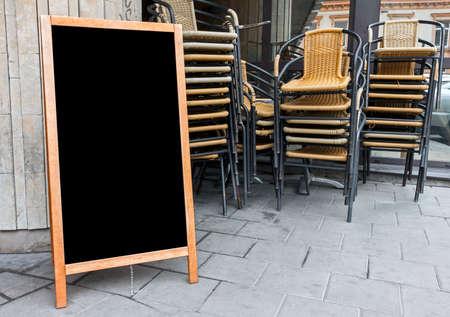 バック グラウンドで積み上げカフェの椅子を広告テキストに空のメニュー ボード 写真素材